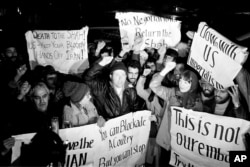 Americans who support Iran's position in the hostage crisis join with Iranians in anti-American demonstrations outside the U.S. Embassy in Tehran , Dec. 15, 1979. (AP Photo/Mohammad Sayad)