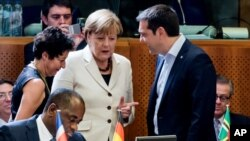 Greek Prime Minister Alexis Tsipras speaks with German Chancellor Angela Merkel at the European Union-Community of Latin American and Caribbean States summit in Brussels, June 10, 2015.