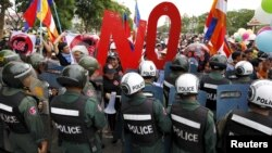 Police officers block a street as protesters march to the Cambodia National Assembly during a protest in Phnom Penh, July 13, 2015.