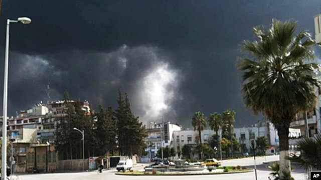 Black smoke rises from buildings in Homs, Syria, March 27, 2012 (AP is unable to independently verify the authenticity, content, location or date of this handout photo.)