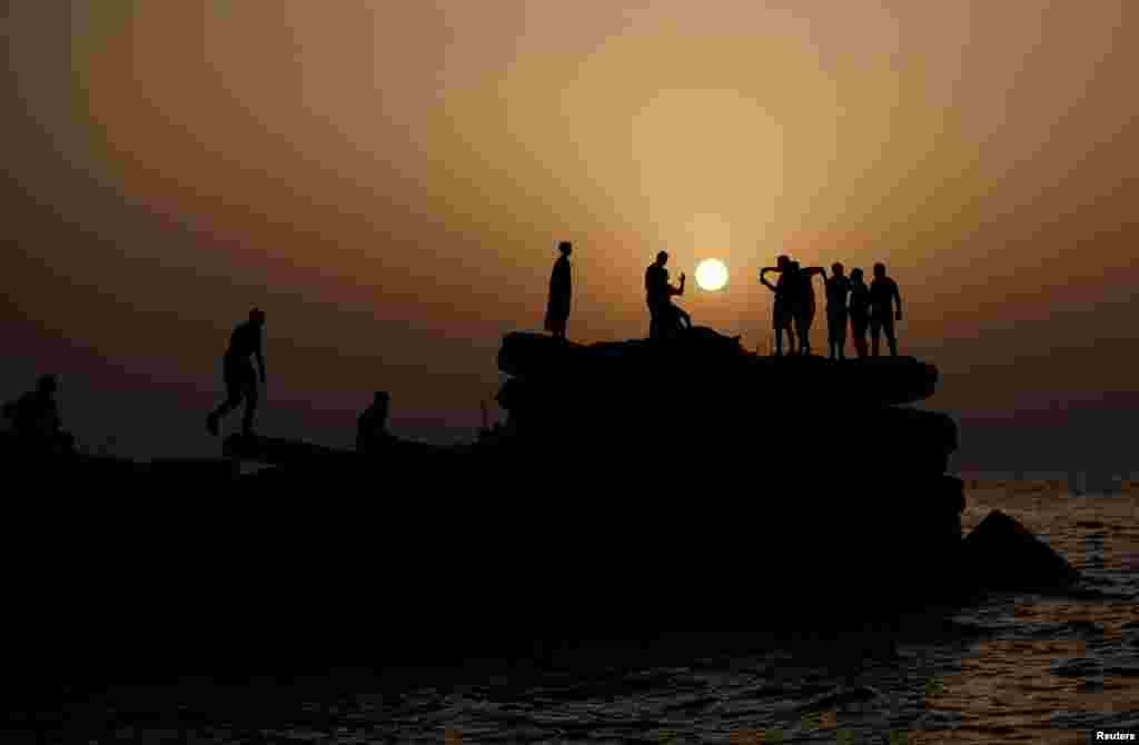 Palestinians are seen during sunset, at the seaport of Gaza City.