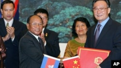 Wu Bangguo, chairman of the Standing Committee of the National People's Congress (NPC) of China, second right, and Heng Samrin, president of the Cambodian National Assembly shake hands after exchanging documents on cooperation between NPC and the Cambodia.