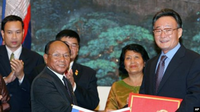 Wu Bangguo, chairman of the Standing Committee of the National People's Congress (NPC) of China, second right, and Heng Samrin, president of the Cambodian National Assembly shake hands after exchanging documents on cooperation between NPC and the Cambodia