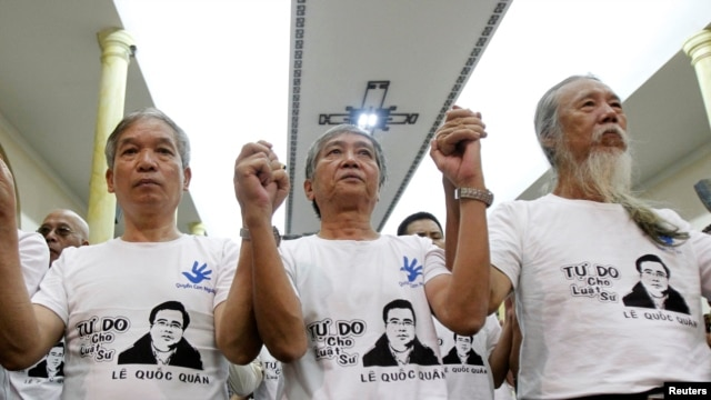 Friends and supporters wearing t-shirts with the image of lawyer Le Quoc Quan hold hands while attending a mass calling for Quan to be freed at Thai Ha church in Hanoi September 29, 2013.