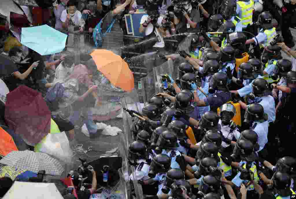 Riot police use pepper spray against protesters after thousands of people block a main road to the financial central district outside the government headquarters in Hong Kong.