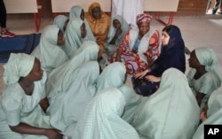 Pakistani activist Malala Yousafzai, far right, speaks with schoolgirls in Maiduguri, Nigeria, July. 18, 2017.