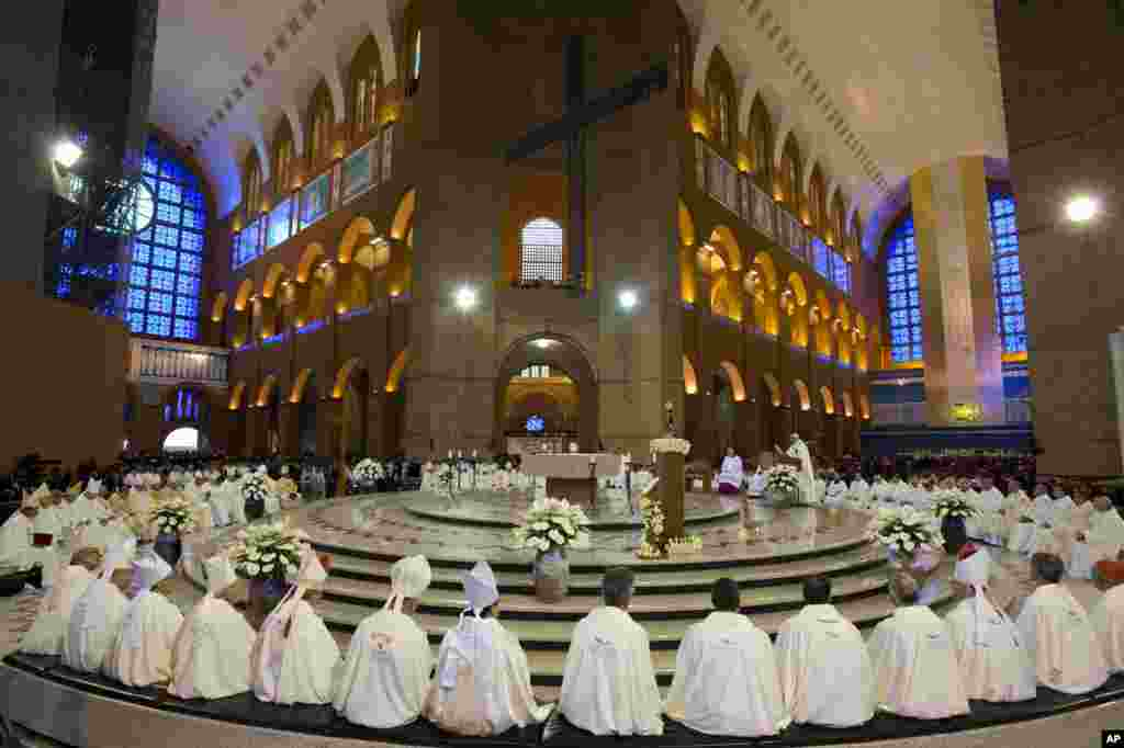 Members of the clergy listen to Pope Francis, center right, as he gives Mass inside Aparecida Basilica in Aparecida, Brazil.