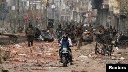 Pengendara motor melewati patroli keamanan di sebuah jalan yang terdampak kerusuhan di New Delhi, India, 26 Februari 2020.