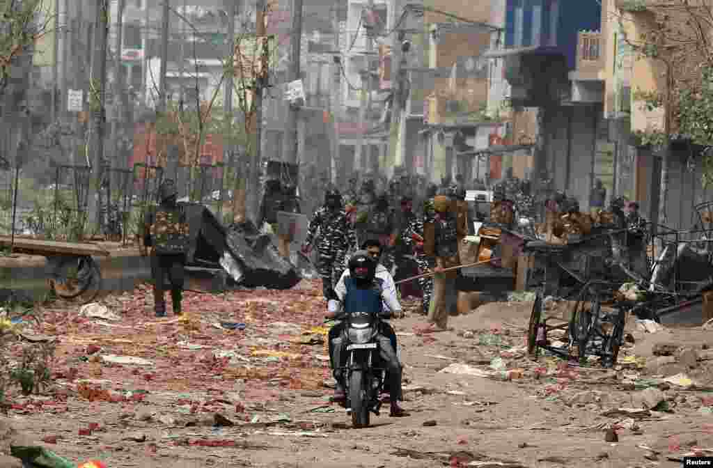 Men ride a motorcycle past security forces patrolling a street in a riot affected area after clashes erupted between people demonstrating for and against a new citizenship law in New Delhi, India.