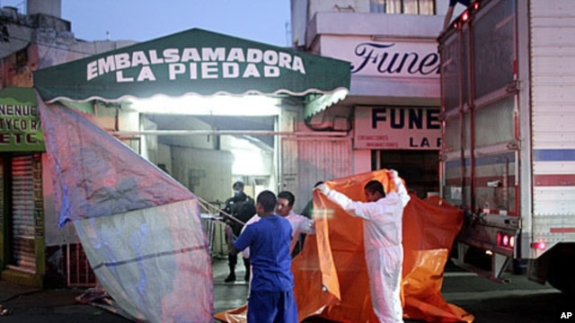 Workers at an embalming facility in Mexico City prepare to unload a truck containing dozens of the 145 bodies found in mass graves in northern Mexico, April 14, 2011