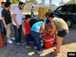 Migrantes centroamericanos hacen fila para recibir alimentos y bebidas donados por la comunidad cerca del Puente Internacional # 1 en Nuevo Laredo, México.