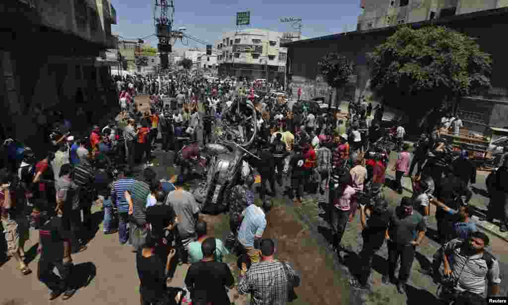 Palestinians gather around the remains of a car which police said was targeted in an Israeli air strike in Gaza City, July 8, 2014.