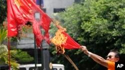 一名菲律宾退休警官在马尼拉焚烧中国国旗,抗议菲律宾人所说的中国侵犯领海行为。(资料照片)