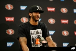 San Francisco 49ers quarterback Colin Kaepernick answers questions at a news conference after an NFL preseason football game against the Green Bay Packers.