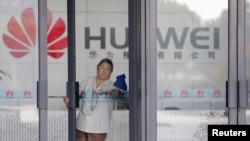一名清洁工在擦拭湖北武汉的华为公司办公楼的玻璃大门。(2012年10月9日资料照)