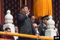 2019年10月1日: 纪念中华人民共和国成立70周年的阅兵式上中国国家主席习近平(左)挥手。
