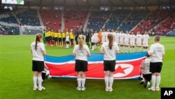 Tim sepakbola putri Korea Utara menyanyikan lagu kebangsaan mereka sebelum pertandingan grup C antara Kolombia melawan Korea Utara yang menandai dimulainya pertandingan Olimpiade Musim Panaas London 2012 di stadion Hampden Park, Glasgow (25/7).