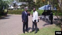 DRC Foreign Minister Raymond Tshibanda (L) and M23 Spokesman Rene Abandi discuss the situation, at DRC peace talks in Kampala, Uganda, Sept. 17. (VOA/A. Hall)