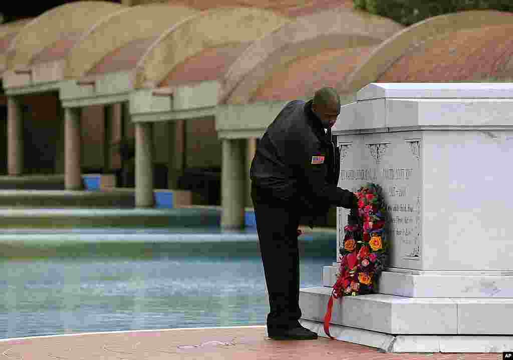 Martin Luther King Jr. Center for Nonviolent Social Change security officer Kevin Baxter places a wreath at the crypts of Martin Luther King Jr., and his wife Coretta Scott King, in Atlanta, Georgia, January 16, 2012. (AP)