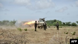 This handout picture released by the AU-UN Information Support Team shows Ugandan soldiers, part of the African Union Mission in Somalia, firing towards Shabab fighters iin the Lower Shabelle region of Somalia, August 30, 2014. (AFP/AMISOM handout/Tobin Jones)