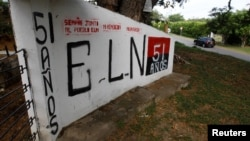 FILE - A graffiti, of rebel group Army Liberation National (ELN) is seen at the entrance of the cemetery of El Palo, Cauca, Colombia, Feb. 10, 2016.