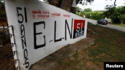 FILE - Graffiti, of rebel group Army Liberation National (ELN), is seen at the entrance of the cemetery of El Palo, Cauca, Colombia, Feb. 10, 2016.