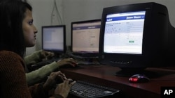 A girl surfs a Facebook page at an Internet cafe in Gauhati, India, Dec. 6, 2011.