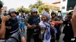 Seorang perempuan ditahan oleh pasukan penjaga keamanan di dekat wilayah Pengadilan Negeri Phnom Penh dimana orang-orang berkumpul menuntut dibebaskannya para aktivis buruh yang diadili (25/4).