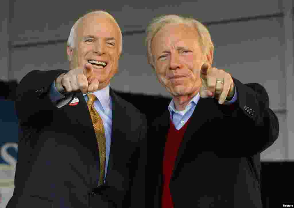 U.S. Republican presidential nominee Senator John McCain (R-AZ) (L) and U.S. Senator Joe Lieberman (I-CT) point to a sign in the crowd at a campaign rally in Grand Junction, Colorado, Nov. 4, 2008, the day of the U.S. presidential election.