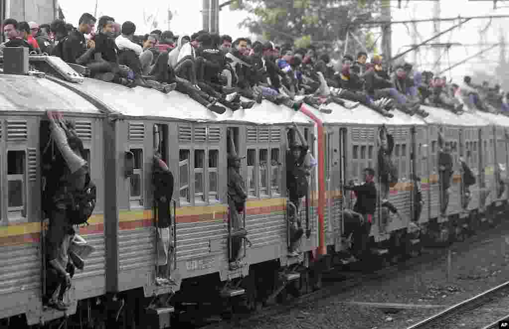 Indonesian men struggle to board a packed commuter train at a station in Jakarta, May 11, 2010. (AP)