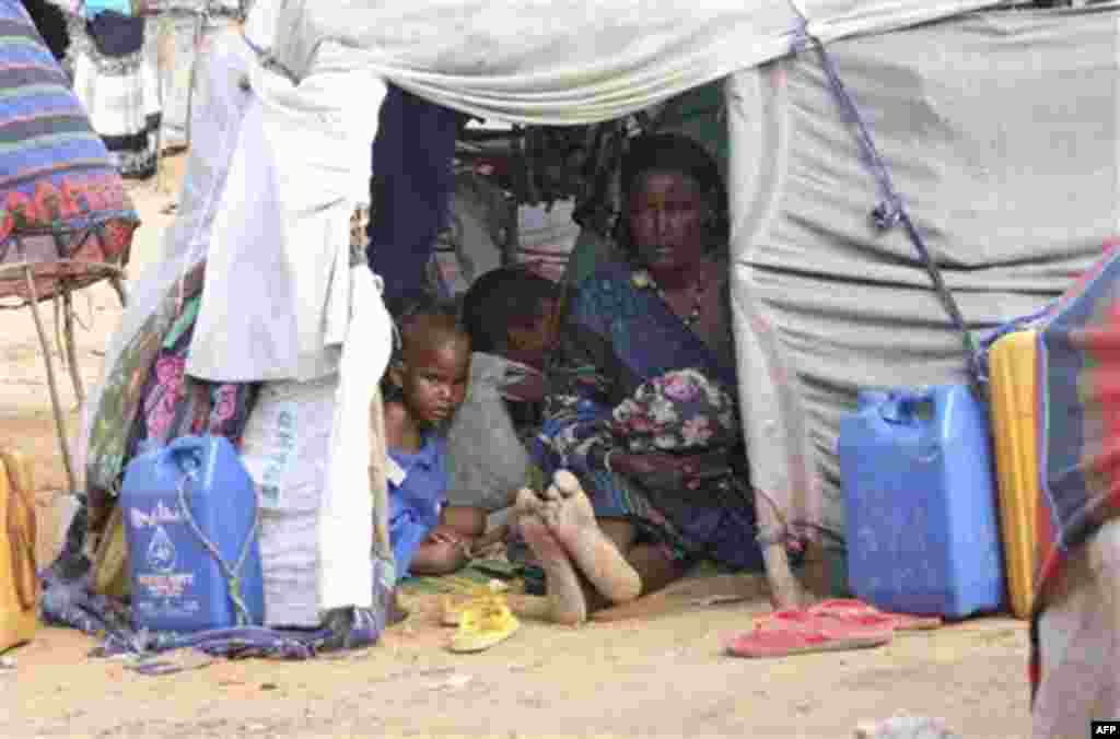 A Somali woman from southern Somalia and her children rest in their makeshift shelter at a camp for displace people in Mogadishu, Somalia, Saturday, Aug, 6, 2011. The United Nations says famine will probably spread to all of southern Somalia within a