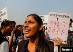 FILE - Students from various colleges hold placards as they shout slogans during a rally against gender discrimination and violence toward women in Mumbai, Dec. 10, 2014.