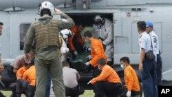 Awak angkatan laut Amerika dari USS Sampson menurunkan jenazah seorang korban pesawat AirAsia dari helikopter di bandara Pangkalan Bun, Jumat (2/1).