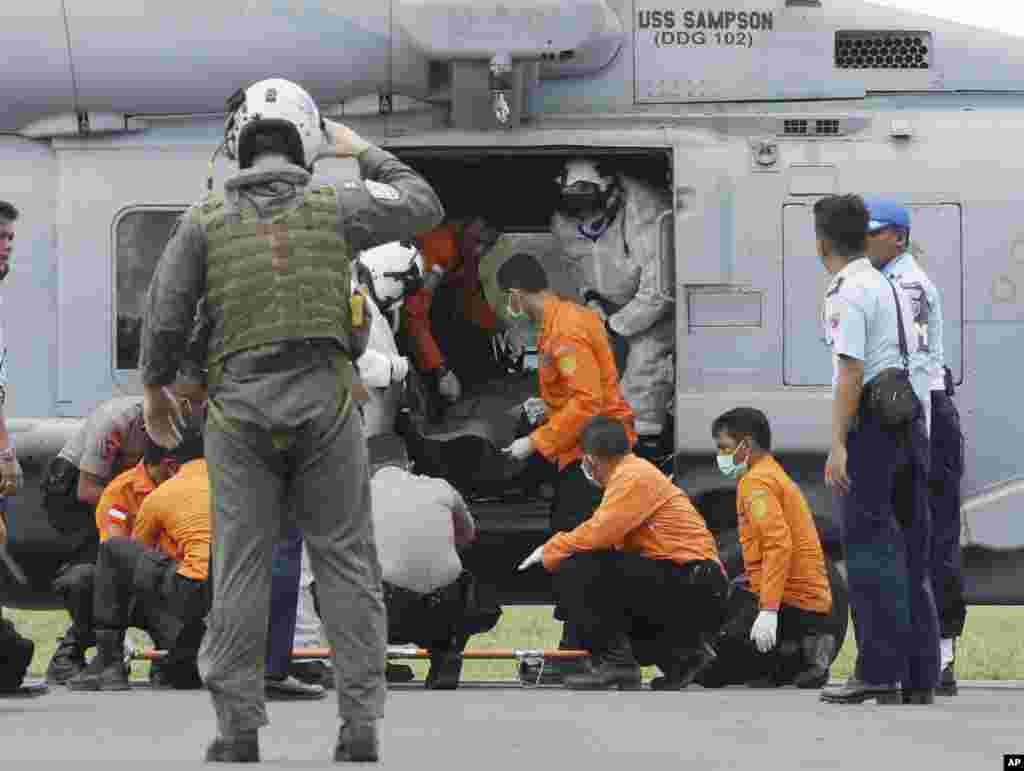 U.S. Navy personnel from USS Sampson unload the body of a victim from AirAsia Flight 8501 from a helicopter as search and rescue personnel and Indonesian policemen receive it in Pangkalan Bun, Indonesia, Friday, Jan. 2, 2015.