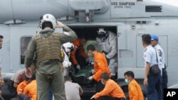 美国桑普森号航母人员将失事亚航班机上的一名遇难者遗体从直升机上运下,遗体由救援人员和印尼警方在印尼的庞卡兰邦获得。