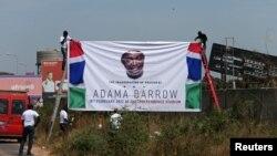 Para pendukung Presiden baru Gambia, Adama Barrow menyiapkan spanduk sebelum kepulangan Barrow ke Banjul, ibukota Gambia, Kamis (26/1).