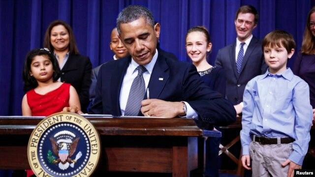El presidente Barack Obama firma la orden ejecutiva sobre la violencia, rodeado de varios niños.