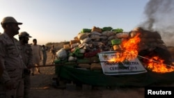 A soldier torches a pile of narcotics during a joint destruction ceremony by the Anti Narcotics Force (ANF) and Pakistan Coast Guards (PCG) on the outskirts of Karachi, Oct. 15, 2015.