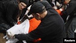 Pendemo melakukan simulasi 'waterboarding', cara penyiksaan oleh pemerintah AS terhadap tahanan. (Foto: Dok)