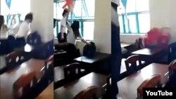 Nhóm nữ sinh dùng ghế nhựa phang liên tiếp vào đầu, đấm túi bụi, kéo và giật tóc một nữ sinh cùng lớp (ngồi) trong khi các em khác đứng xem. (Ảnh từ clip trên YouTube).
