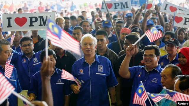 Malaysia's Prime Minister Najib Razak (C) waves a national flag as he sings patriotic songs with supporters during an election campaign rally in Rawang, outside Kuala Lumpur April 28, 2013.