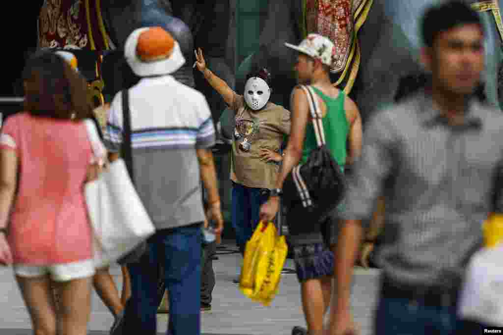 A masked demonstrator gestures during a brief protest against military rule at a shopping mall in Bangkok, June 1, 2014.