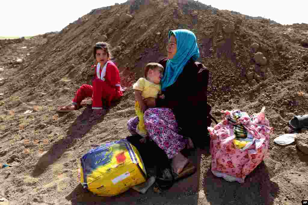 An Iraqi woman who fled her village holds her daughter near a Kurdish checkpoint, in the Khazer area between Mosul and Irbil, northern Iraq, June 26, 2014.