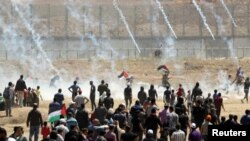 Palestinian demonstrators run for cover from tear gas canisters fired by Israeli forces during a protest marking the 71st anniversary of the 'Nakba', or catastrophe, near the Israel-Gaza border fence, east of Gaza City, May 15, 2019.