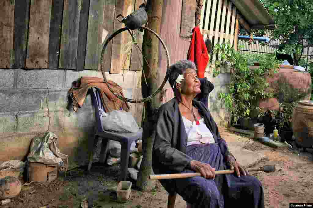 A great-grandmother, now in her nineties and having spent a lifetime rice farming, sits contentedly in her garden in northeastern Thailand without the need for internet, television or telephone, Sept. 4, 2014. (Photo taken by Matthew Richards/Thailand/VOA
