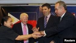 美国国务院亚太事务助理国务卿坎贝尔(右)、美国国防部亚太事务助理部长(右起第二)、菲律宾驻美大使奎西亚和菲律宾外交部负责政策事务的副部长巴西利奥(左)在马尼拉举行的联合记者会上握手(2012年12月12日)