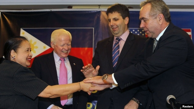 U.S. Assistant Sec. of State for East Asian and Pacific Affairs Kurt Campbell (R), U.S. Assistant Sec. of Defense for Asian and Pacific Security Affairs Mark Lippert (2nd R), Philippines ambassador to the U.S. Jose Cuisia, Philippines Foreign Affairs Undersecretary for Policy Erlinda Basilio (L)  join hands during a joint news conference in Manila, December 12, 2012.