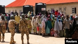 Security officers are called to control some of the internally displaced people at the Bakkasi camp. The people were upset at camp authorities for what they say is poor distribution of food rations, in Borno, Nigeria, on August 29, 2016.