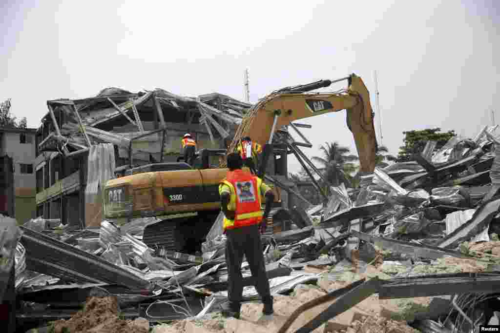 An emergency official watches an excavator dig through the rubble of a collapsed building in the Victoria Island district of Lagos, Nov. 5, 2013.