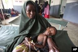A woman holds her malnourished child on arrival at Banadir hospital in Mogadishu, Somalia, July 7, 2011